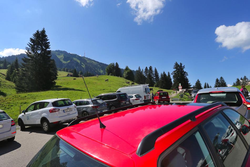 Autos von Ausflüglern stehen auf dem voll belegten Parkplatz der Alpe Kammeregg im strahlenden Sonnenschein. Viele Gemeinden haben nun mit hohen Parkgebühren auf die Flut an Touristen reagiert.