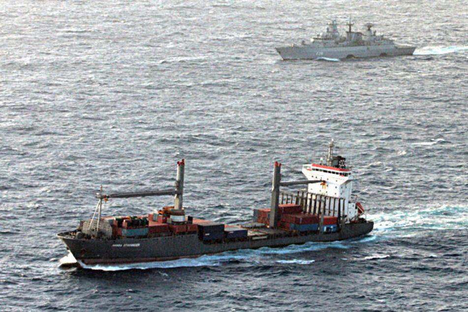 """Die Fregatte """"Brandenburg"""" der Deutschen Marine (im Hintergrund) begleitet das Handelsschiff """"Hansa Stavanger""""."""
