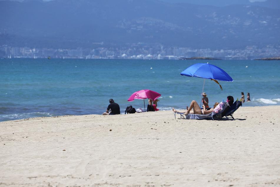 Badegäste liegen am Playa de Palma.