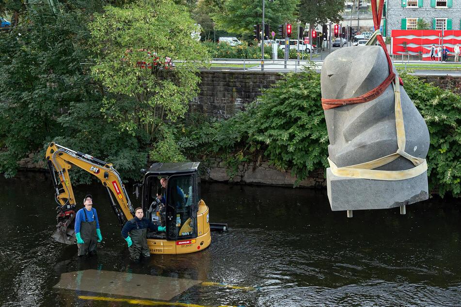 """Die Skulptur des Elefanten """"Tuffi"""" hängt über der Wupper an einem Kran. Das Hochwasser in Wuppertal hat einen Störstein in Form eines sitzenden Elefanten verschwinden lassen."""