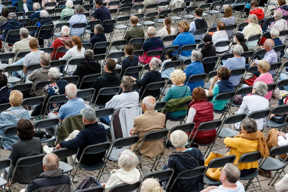 Zuhörer eines Open-Air-Konzerts sitzen auf ihren Plätzen. Seit Samstag können Veranstalter und Wirte in Hamburg selbst entscheiden, ob sie nur Geimpfte und Genesene einlassen wollen.