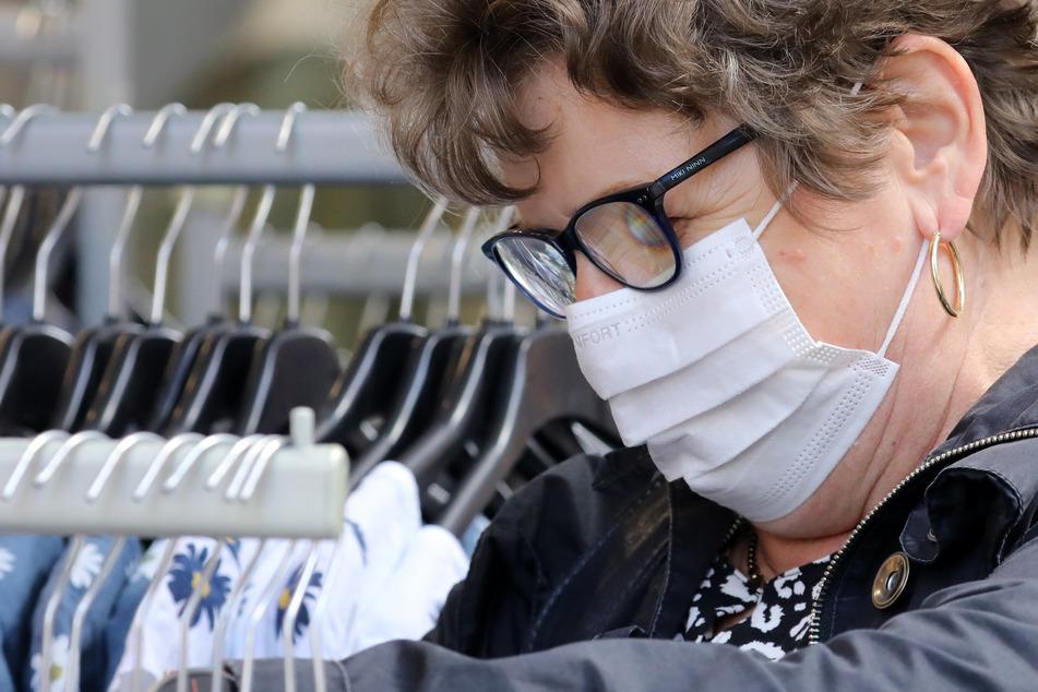 Ein Frau mit einer Mund-Nasen-Bedeckung schaut sich die Auslagen eines Bekleidungsgeschäftes an.