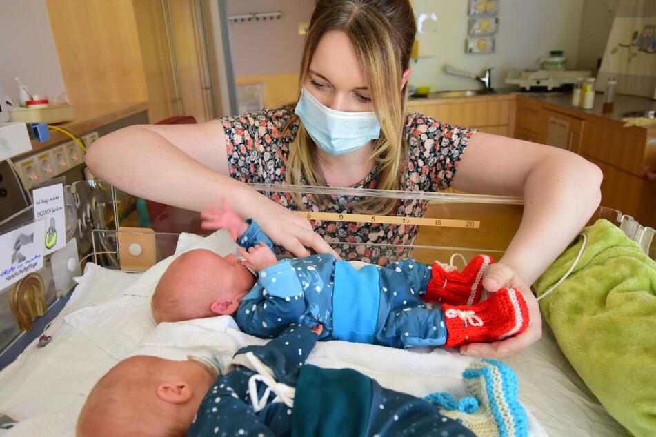 Spenden für die Uniklinik: Mama Stephanie mit ihren Zwillingen Fiete und Till, die beide die handgestrickten Söckchen tragen.