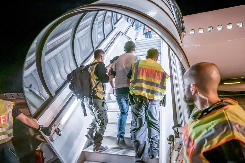 Polizeibeamte begleiten einen Afghanen auf dem Flughafen in ein Charterflugzeug, das ihn zurück in sein Heimatland bringt. (Archivbild)