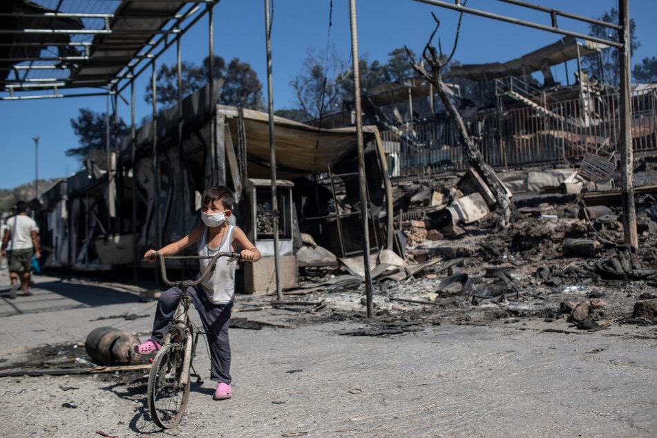 Ein Junge steht mit einem Fahrrad in dem abgebrannten Flüchtlingslager.