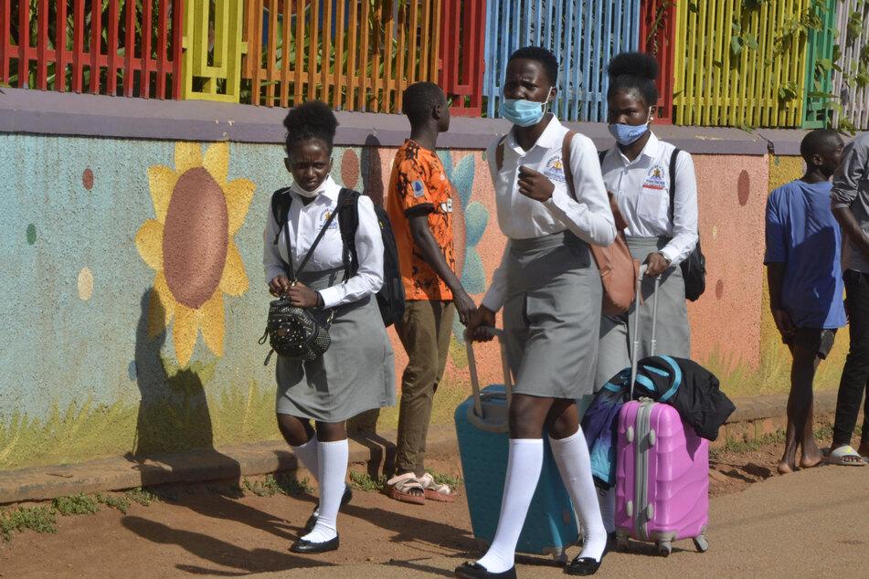 Schülerinnen verlassen ihre Schule in Ugandas Hauptstadt Kampala. Landesweit wurden Bildungseinrichtungen geschlossen, nachdem die Anzahl der Corona-Infektionen gestiegen ist.