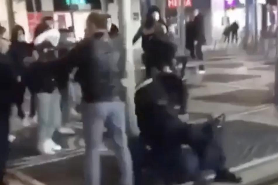 Ein Beamter drückt einen Mann mitten auf der Zeil auf den Boden.