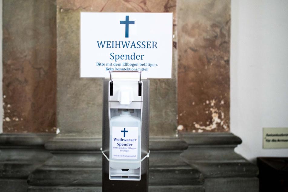 Ein Spender mit Weihwasser steht in der Wallfahrtskirche Basilika Birnau am Bodensee.