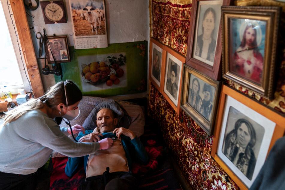 Dr. Viktoria Mahnych untersucht einen Corona-Patienten mit einem Stethoskop in seinem Haus im Dorf Iltsi.