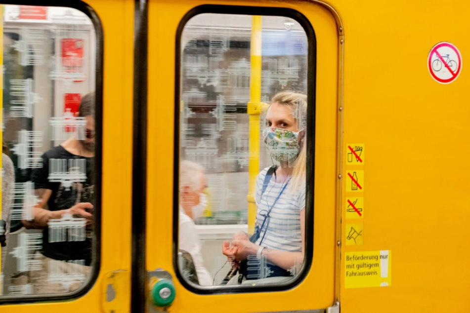 Eine Frau mit Mundschutz ist in einer U-Bahn zu sehen. (archivbild)