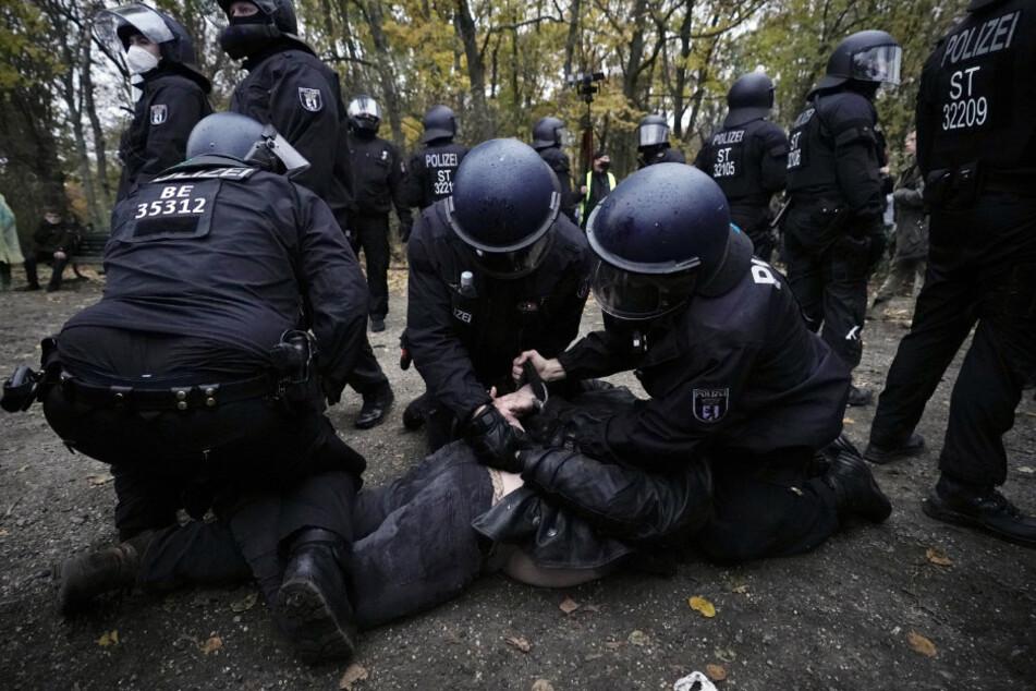 Polizisten legen einem Mann bei einer Demonstration gegen die Corona-Einschränkungen der Bundesregierung Handschellen an.