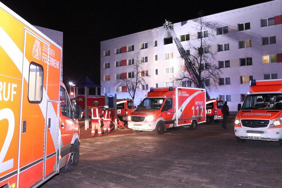 Einsatzwagen der Feuerwehr stehen vor einem Wohnhaus in Berlin-Marzahn.