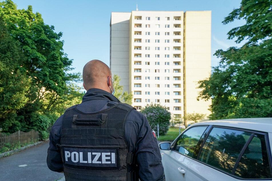 Polizeibeamte bewachen die Ausgänge des Hochhauses.