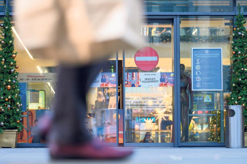 Ein Passant geht mit einer Papiertüte auf der Einkaufsstraße Prager Straße entlang.