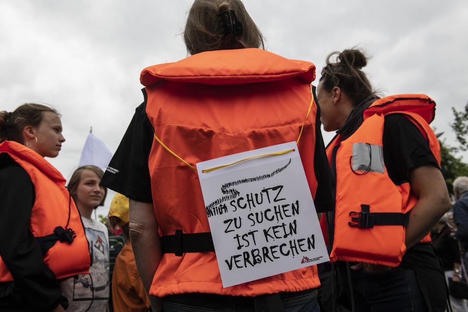 Mit Rettungswesten stehen Teilnehmer an der Demonstration der Organisation Seebrücke im Juli am Bundeskanzleramt.