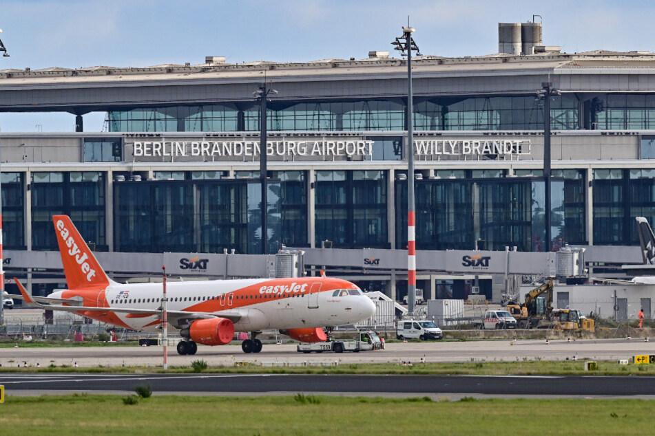 """Ein Passagierflugzeug der britischen Fluggesellschaft Easyjet wird über das Vorfeld am Terminal 1 vom Hauptstadtflughafen Berlin Brandenburg """"Willy Brandt"""" (BER) gezogen."""