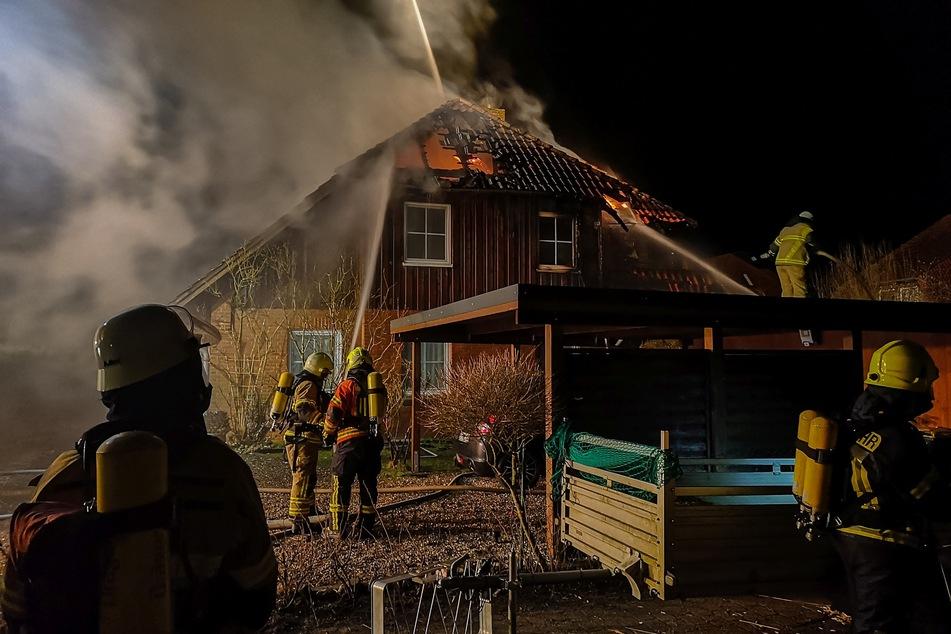 Die Feuerwehrleute löschen das brennende Dach.