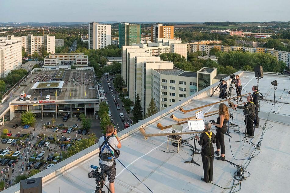 Vier Dresdner Sinfoniker mit ihren Alphörnern auf einem Hochhaus-Dach.