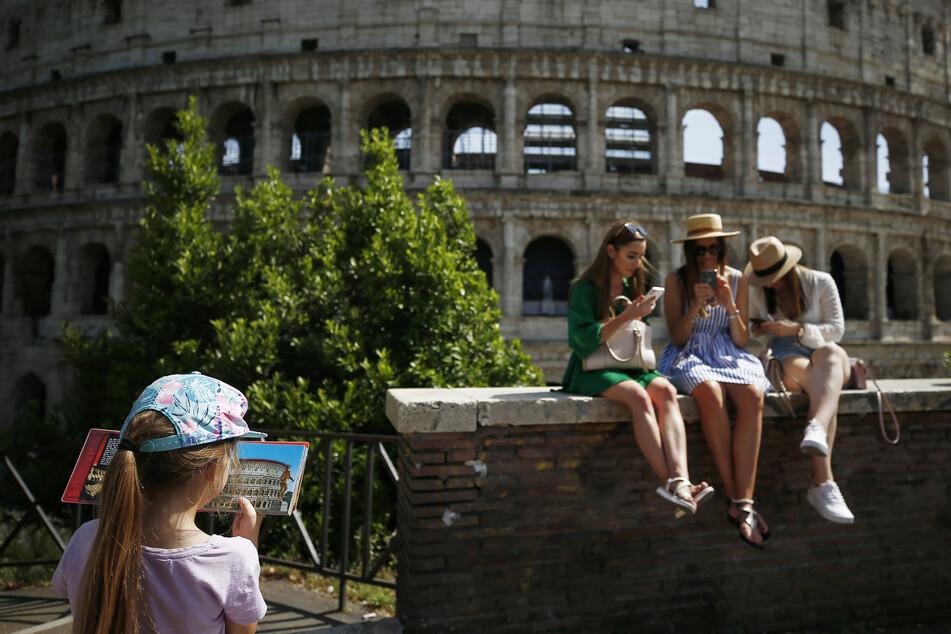 Eine Gruppe junger Frauen sitzt vor Kolosseum. In Italien hat der späte Beginn der Tourismussaison den Neustart des Urlaubssektors nach der Lockerung von Corona-Beschränkungen gebremst.