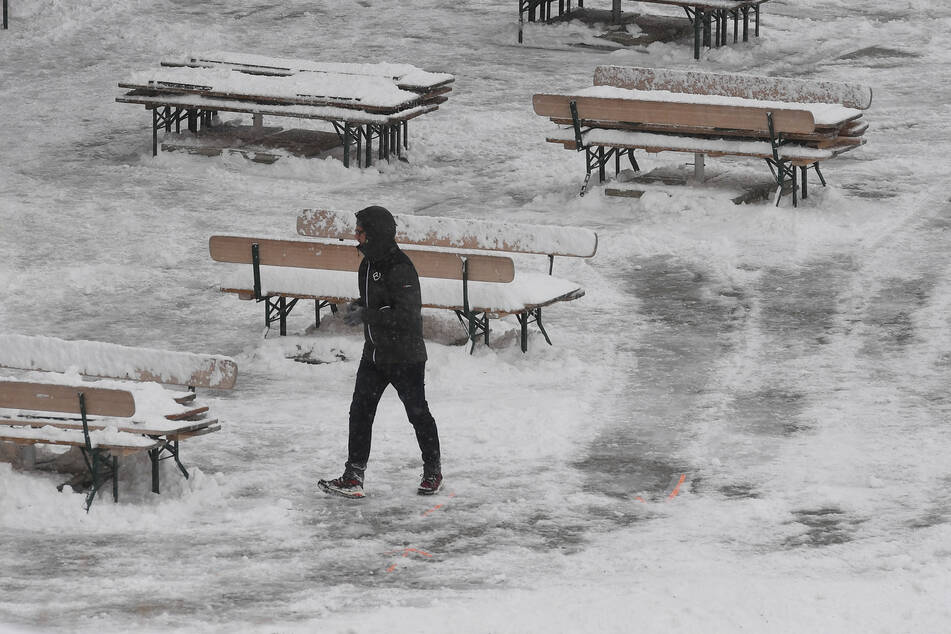 Ein Mann geht über die verschneite Terrasse der Bergstation am Osterfelderkopf im Wettersteingebirge nach einem Temperatursturz.