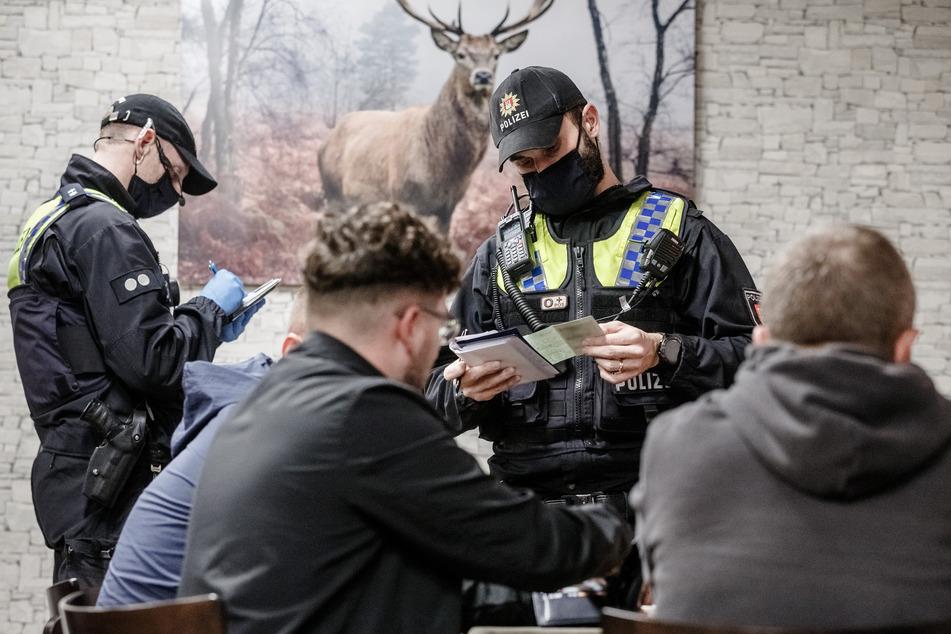 Polizisten kontrollieren in einer Bar die Einhaltung der Corona-Vorgaben, hauptsächlich, ob die Einträge in der Gästeliste mit den Ausweispapiere der Besucher übereinstimmen. Im Ergebnis waren einige Angaben unvollständig, falsch, oder die Besucher konnten sich nicht ausweisen.