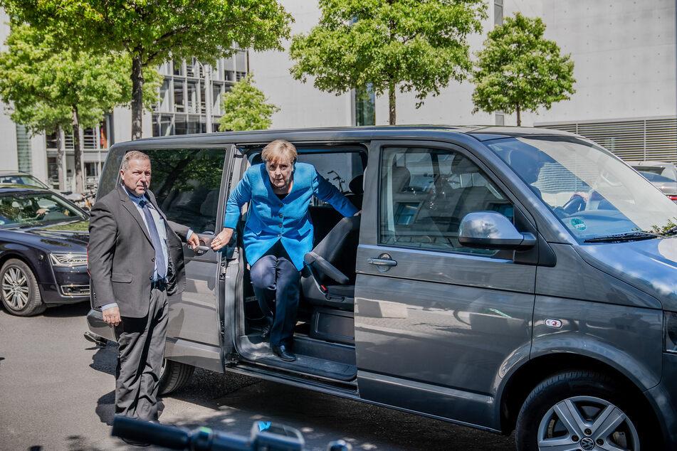 Bundeskanzlerin Angela Merkel (CDU) steigt neben einem Bodyguard vor dem Bundestag aus einem VW-Bus. Viele Bundestagsabgeordnete nehmen die Dienste des betroffenen Chauffeurdiensts in Anspruch.