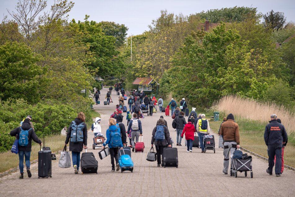 Spiekeroog: Touristen mit Koffern laufen über die Insel.