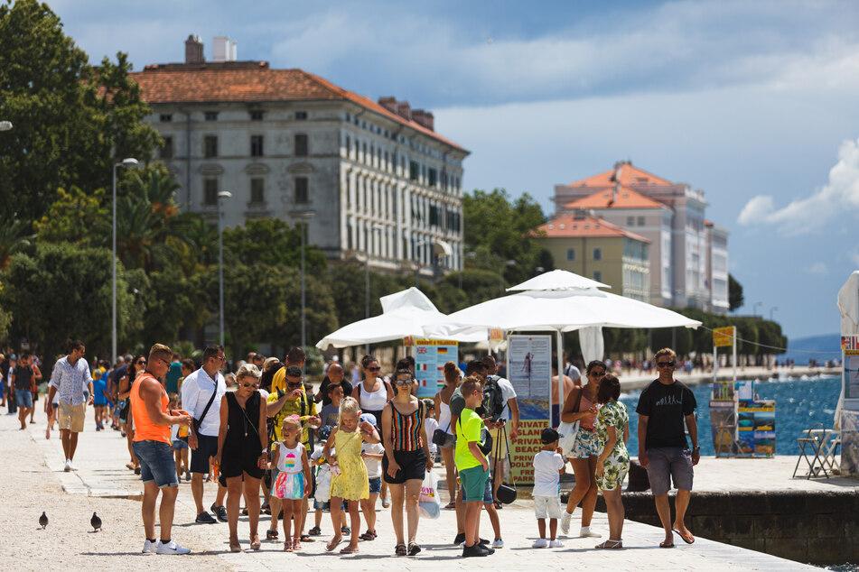 Touristen spazieren an der Uferpromenade von Zadar entlang.