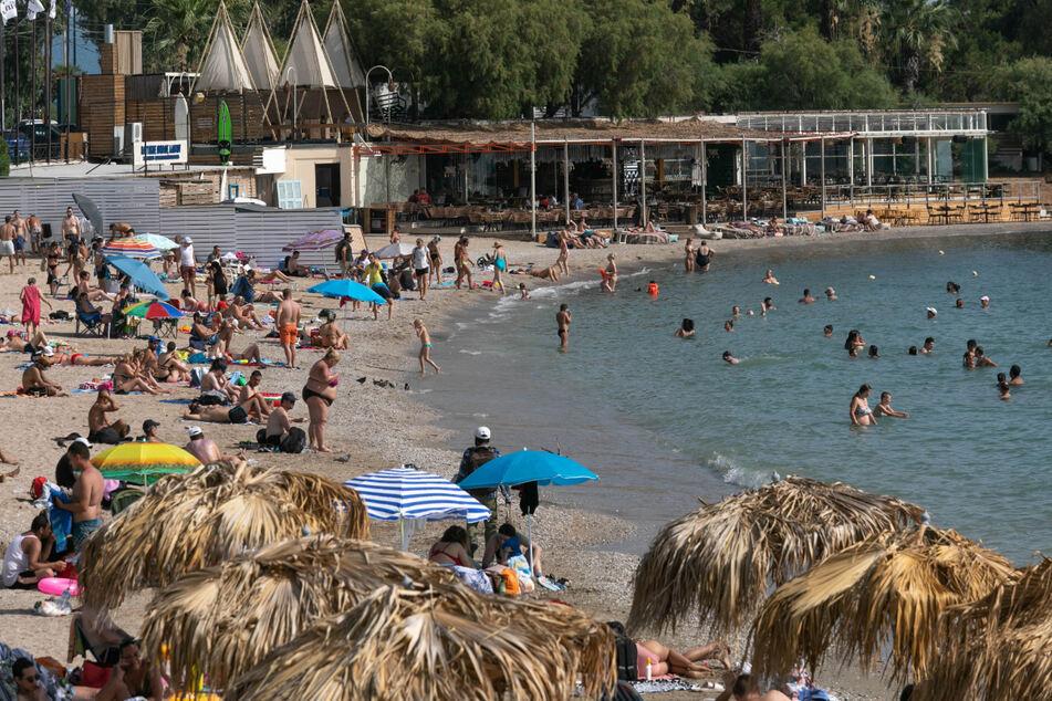 Athen: Menschen genießen das warme Wetter am Strand und baden im Meer.