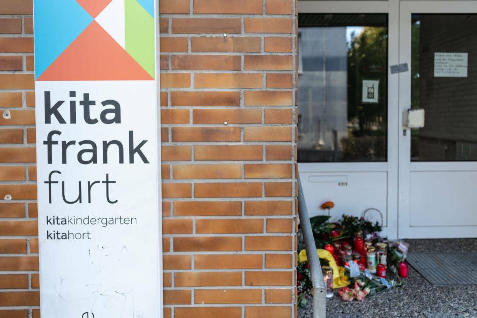 Blumen und Kerzen (r) sind am Eingang zu der Kindertagesstätte im Stadtteil Seckbach abgelegt (Archivbild).