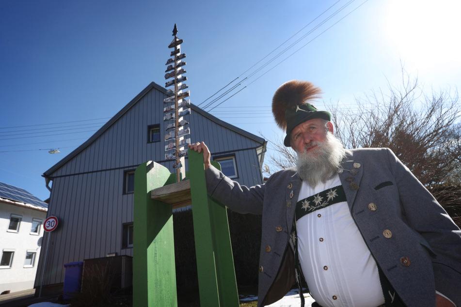 Franz Merk, Vorsitzender des Altusrieder Trachtenvereins, steht an einer Halterung für einen Maibaum in der wegen der Corona bedingten ausgefallenen Maibaumfeier nur eine 1,10 Meter große Nachbildung befestigt ist.