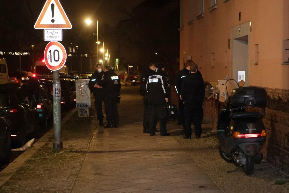 Polizisten stehen an einem Haus in Schöneberg.