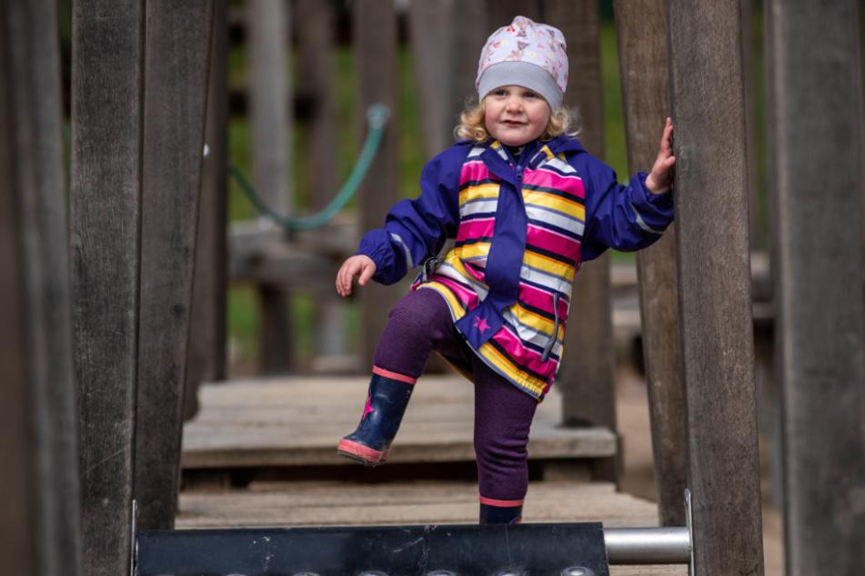 Die zweijährige Elli-Marie tobt auf dem Spielplatz auf der Bürgerwiese in Grevesmühlen auf einem Klettergerüst.