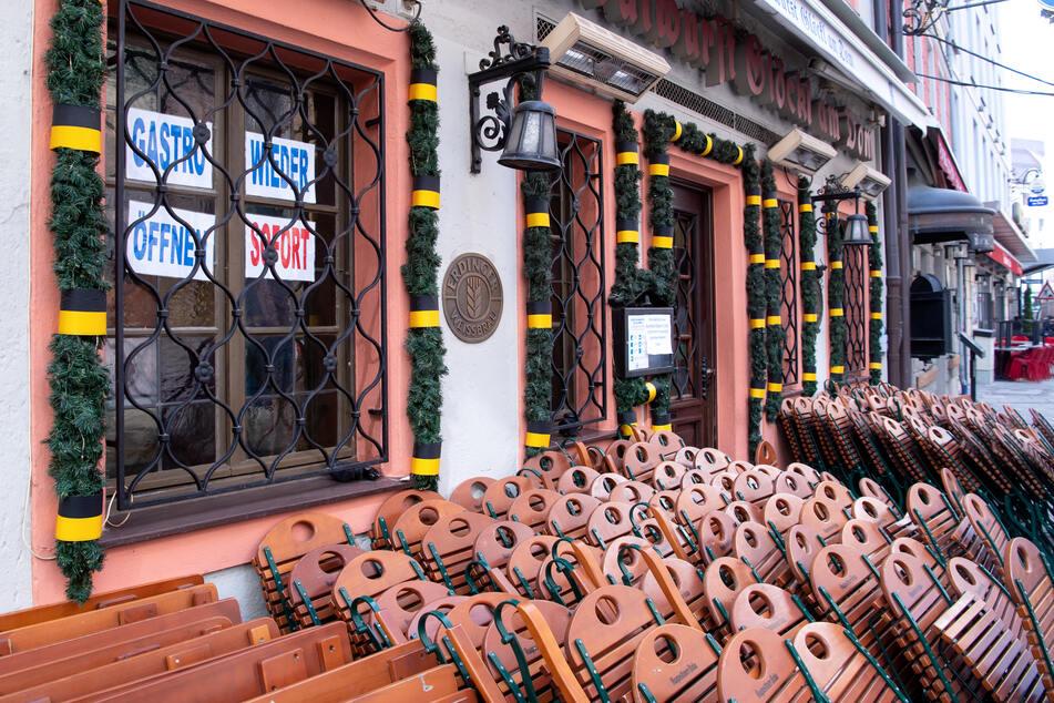 """Tische und Stühle stehen vor einem Restaurant. Im Fenster hängen Zettel mit der Aufschrift """"Gastro wieder öffnen - sofort""""."""