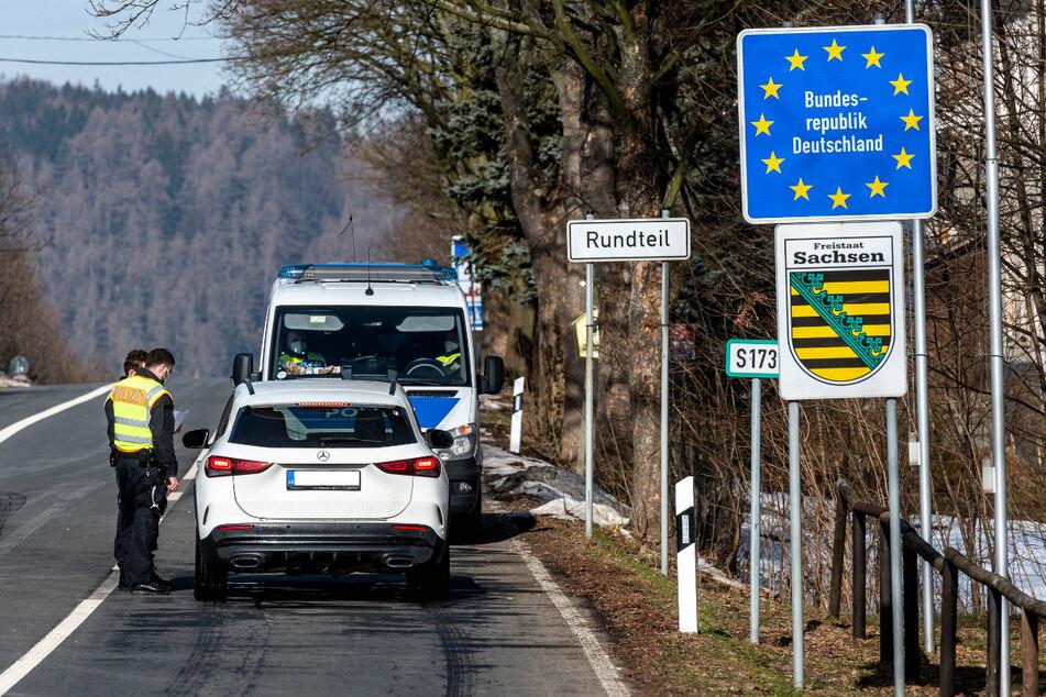 Deutsche Polizeibeamte kontrollieren ein Fahrzeug am tschechisch-deutschen Grenzübergang Petrovice/Bahratal im Erzgebirge. Die Zahl der Menschen, die an den Grenzen abgewiesen werden, ging den Angaben zufolge in den vergangenen Tagen zurück, Reisende verhalten sich zunehmend regelkonform.