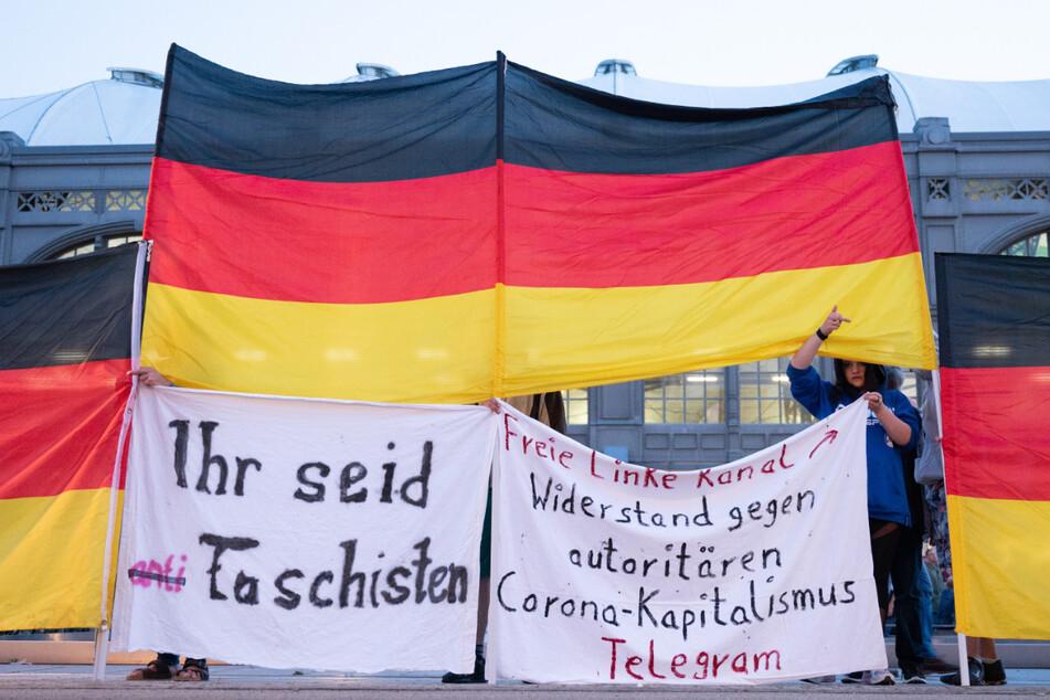 Die Teilnehmerin des Protests steht hinter einer Deutschland-Flagge und hält Spruchbänder hoch.