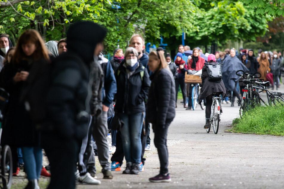 Zahlreiche Impfwillige warten auf den Gehwegen rund um eine Turnhalle einer Schule in Neukölln, wo eine Schwerpunktimpfung gegen Corona stattfindet.