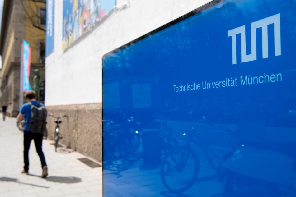 Ein Student geht vor dem Haupteingang der Technischen Universität München (TUM) entlang.