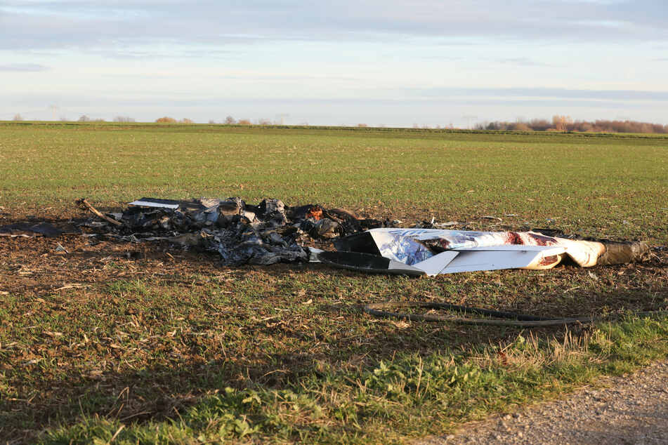 Ausgebrannte Überreste eines abgestürzten Kleinflugzeuges liegen an der Unfallstelle.