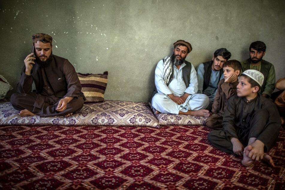 Matiullah Ruhani (l.), Sprecher der Taliban für Kundus, wird während eines Telefonats von anderen Taliban und Kindern beobachtet.