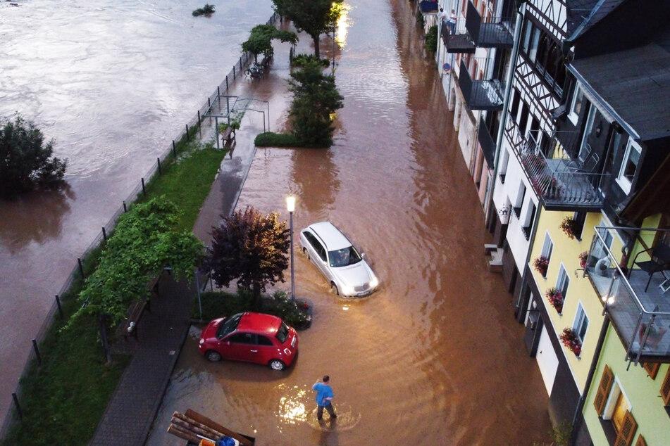 Autos versuchen auf einer überfluteten Straße vorwärts zu kommen. Die Mosel ist in dieser Woche in der Ortschaft Zell (Rheinland-Pfalz) über die Ufer getreten.