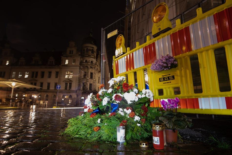 Blumen und Kerzen liegen an der Stelle in Dresden, an der zwei Touristen mit einem Messer von einem Islamisten angegriffen wurden. Dabei starb ein Mann.