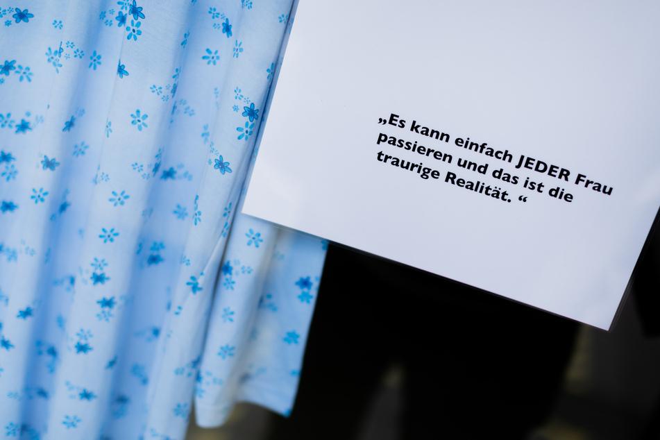 """Die Ausstellung """"Was ich anhatte..."""" in Aachen: """"Es kann einfach JEDER Frau passieren und das ist die traurige Realität"""" steht auf einem der Zettel, die neben den Kleidungsstücken vergewaltigter Frauen in dem Schaufenster aufgehängt sind."""