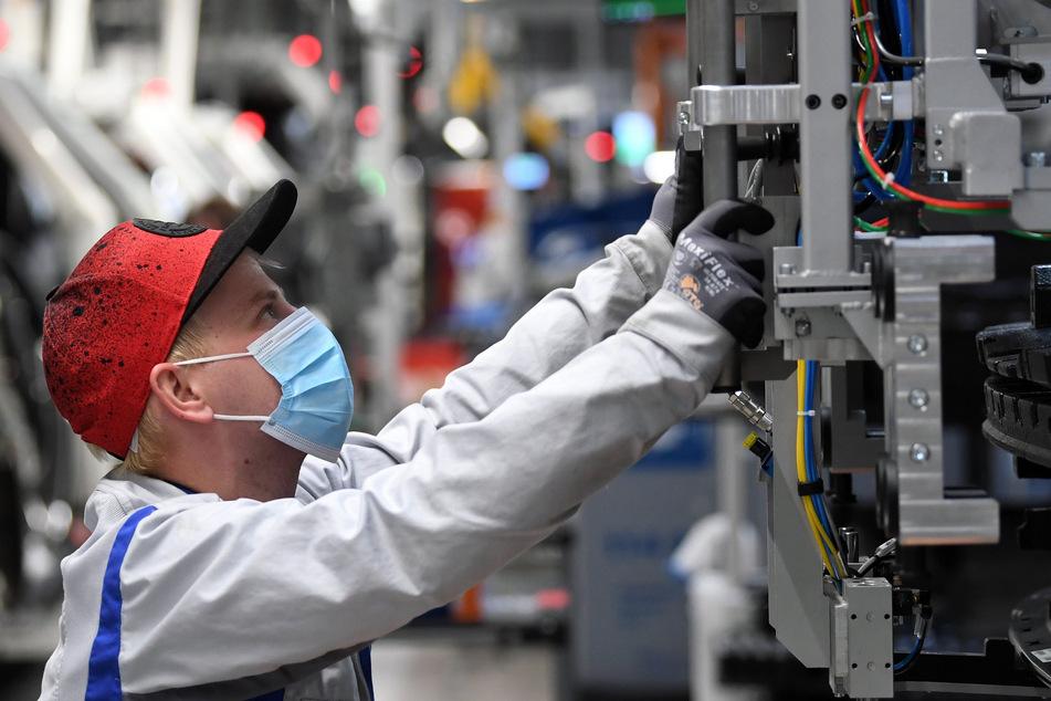 Ein Mitarbeiter von Volkswagen Sachsen arbeitet mit Mundschutz in einem Fahrzeugwerk in Zwickau.