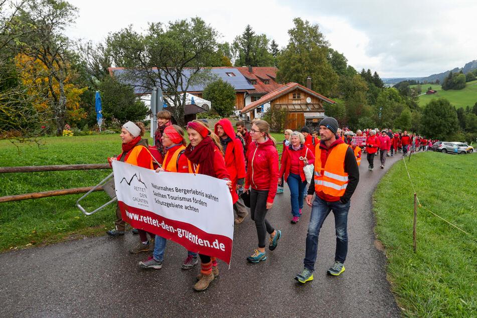 Teilnehmer einer Demonstration gegen ein Bergbahnprojekt am Grünten im Allgäu ziehen durch Rettenberg-Kranzegg zum alten Grüntenlift.
