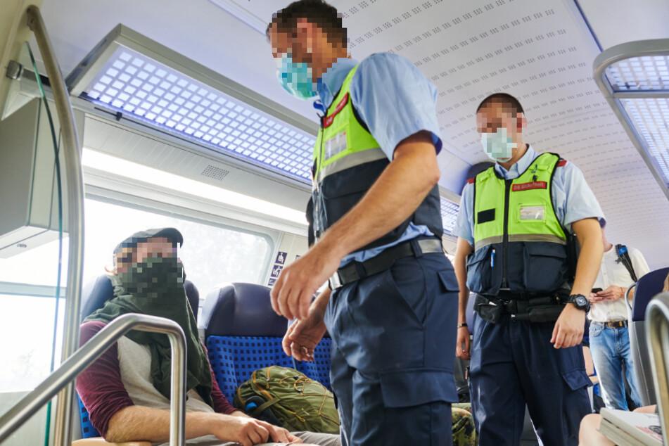 Beamte der Bundespolizei kontrollieren in einem Zug, ob die Maskenpflicht eingehalten wird. (Symbolfoto)