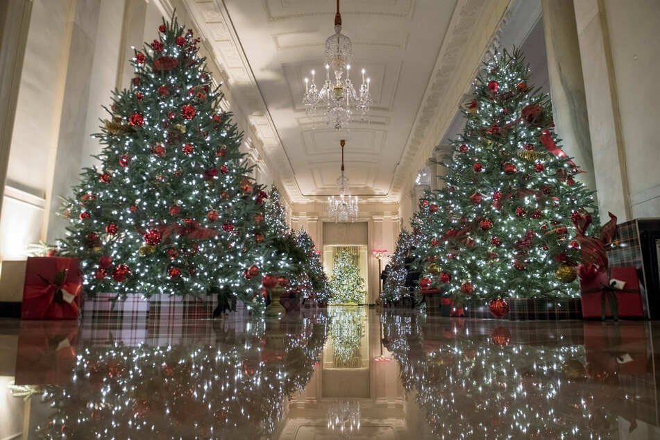 The Cross Hall, which connects the State Dining Room and the East Room, is decorated with festive Christmas trees.