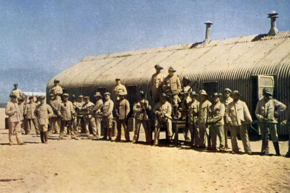 Reiter der sogenannten kolonialen Schutztruppe beim Gewehrreinigen in Swakopmund (vor 1910).