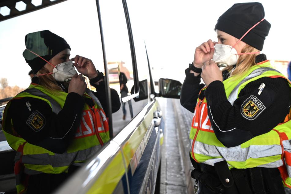 Weil am Rhein: Eine Bundespolizistin zieht sich am Grenzübergang zur Schweiz vor einer Kontrolle eine Atemmaske auf.
