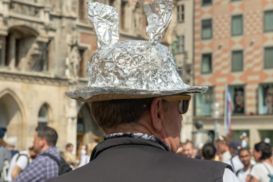 Ein Demonstranten mit einem Strohhut der mit Aluminium bespannt ist, steht in einer Menschenansammlung auf dem Marienplatz. (Symbolbild)